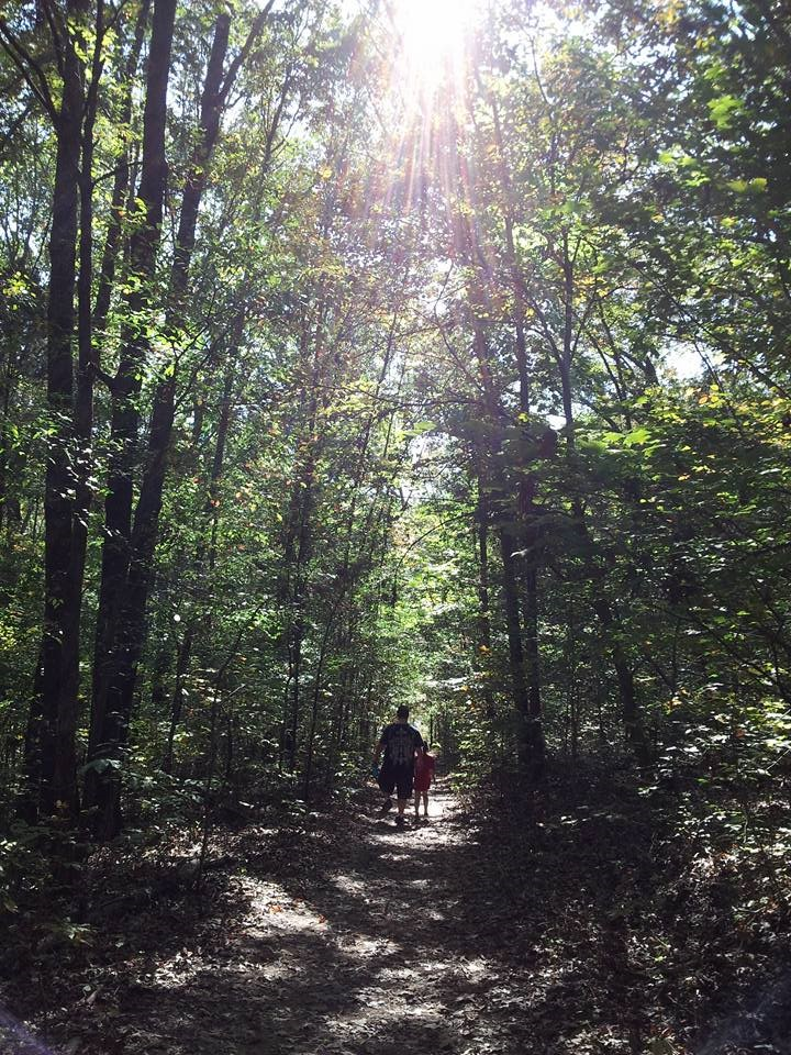 A child and father walks a trail in the woods at Dunbar Cave State Park.