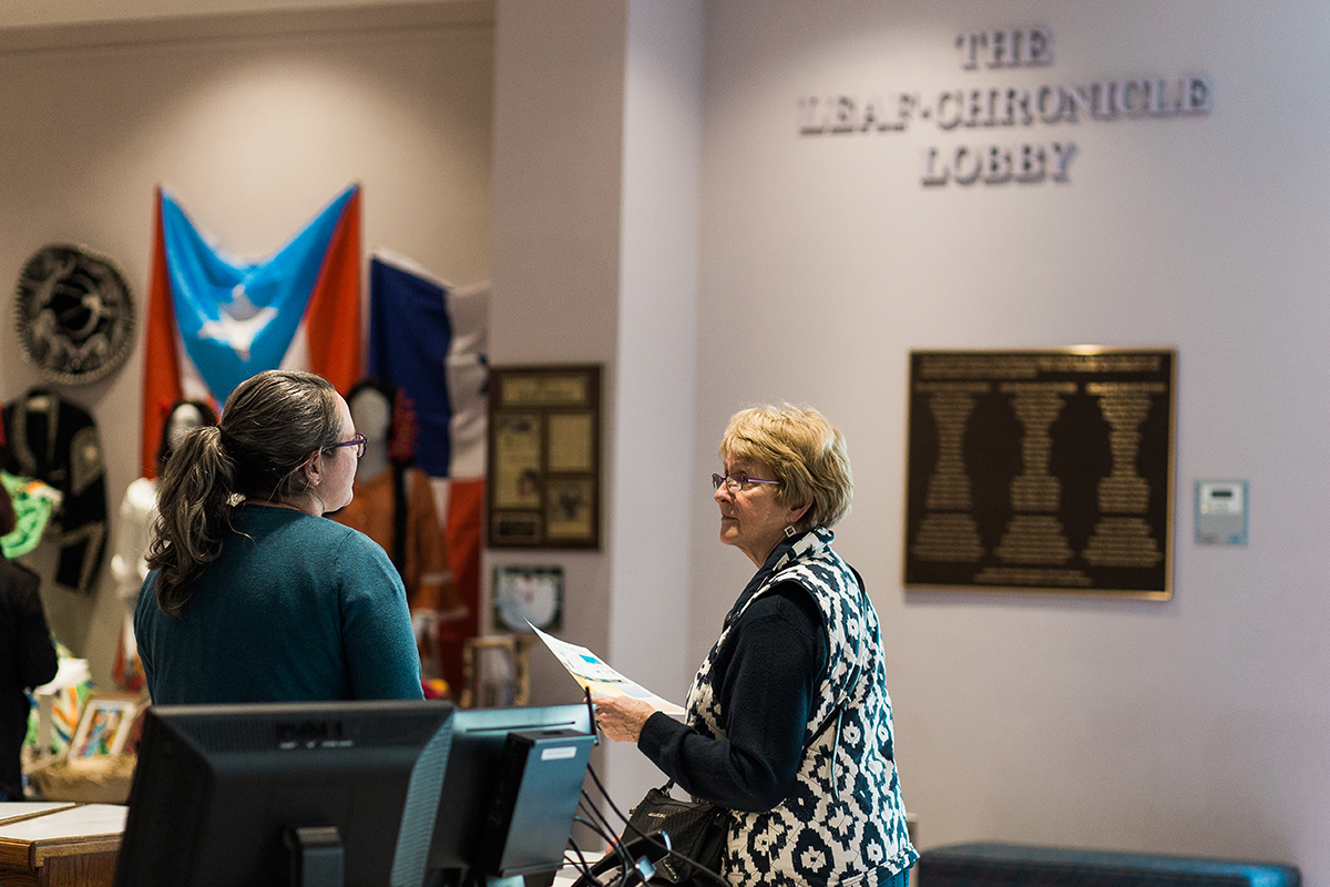 A Museum visitor talks to the front desk associate in the lobby of the Museum.