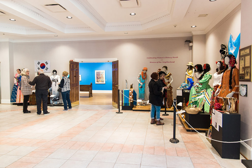Visitors explore the Museum lobby exhibit featuring ornate dresses from different cultures.