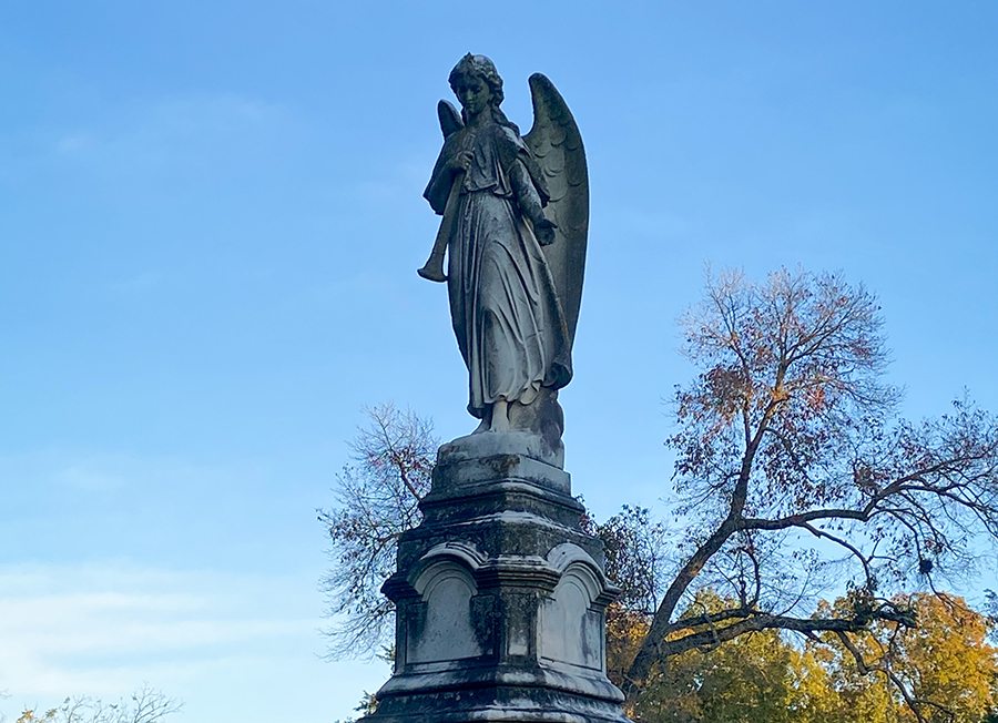 Ornate young, female angel holding a trumpet atop a marker at Greenwood Cemetery.