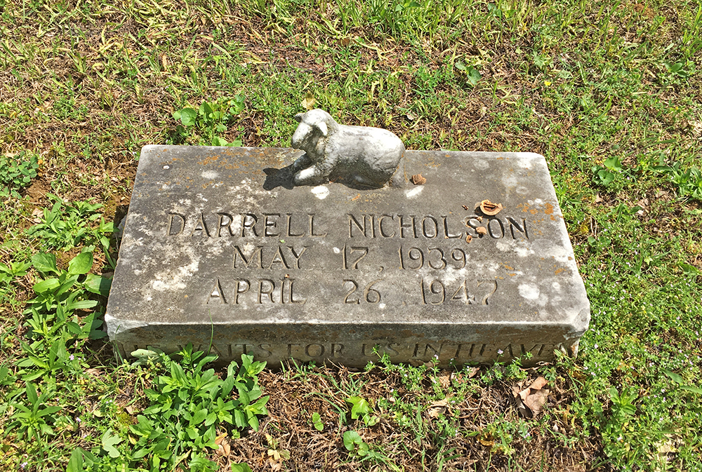 Headstone with an ornate lamb on it. Headstone reads 'Darrell Nicholson, May 17, 1939 - April 26, 1947.