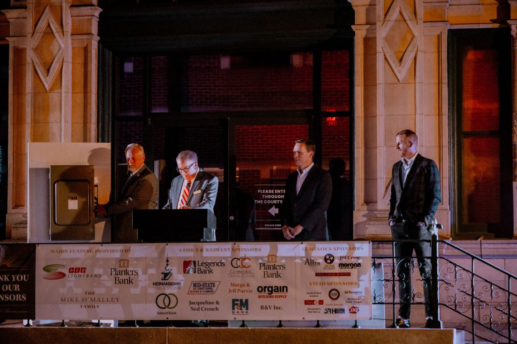Executive Director Frank Lott stands on steps of the Museum along with sponsor representatives to turn on the roof lights.
