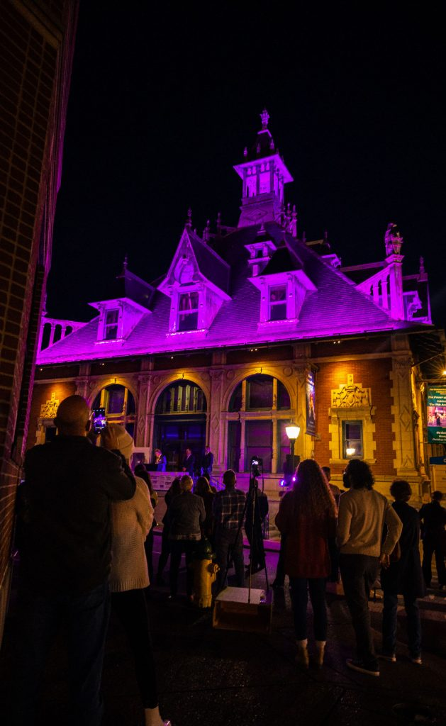 The Customs House Museum & Cultural Center illuminated in purple for the crowd.