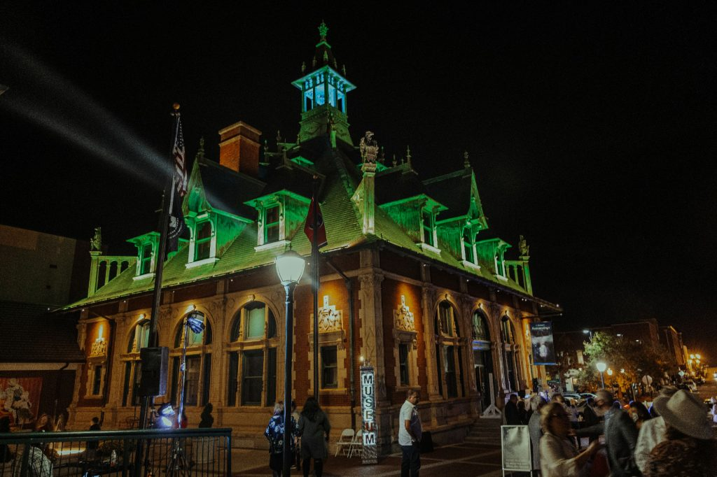 The Customs House Museum & Cultural Center illuminated in green for the crowd.