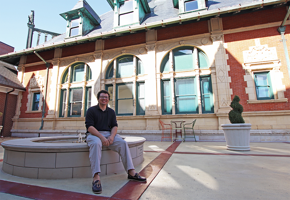 Marketing Intern Alijah Poindexter sits on the fountain in the courtyard of the Customs House Museum & Cultural Center