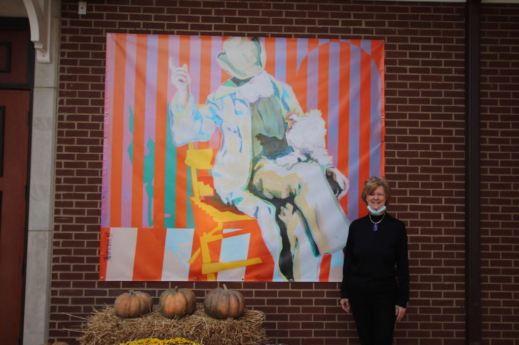 Jacqueline Crouch stands in front of a new banner in the Museum courtyard of a painting she and her husband donated to the Museum.