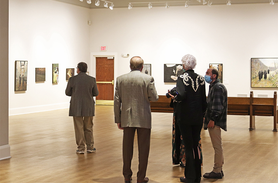 Museum visitors admire paintings hanging in a Museum gallery.