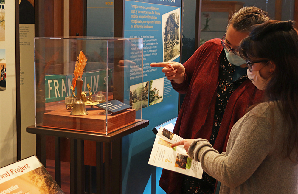 Mom and daughter check out quill pen artifact in the Becoming Clarksville exhibit. Mom points to artifact and daughter points to Museum Discovery Quest in her hands.