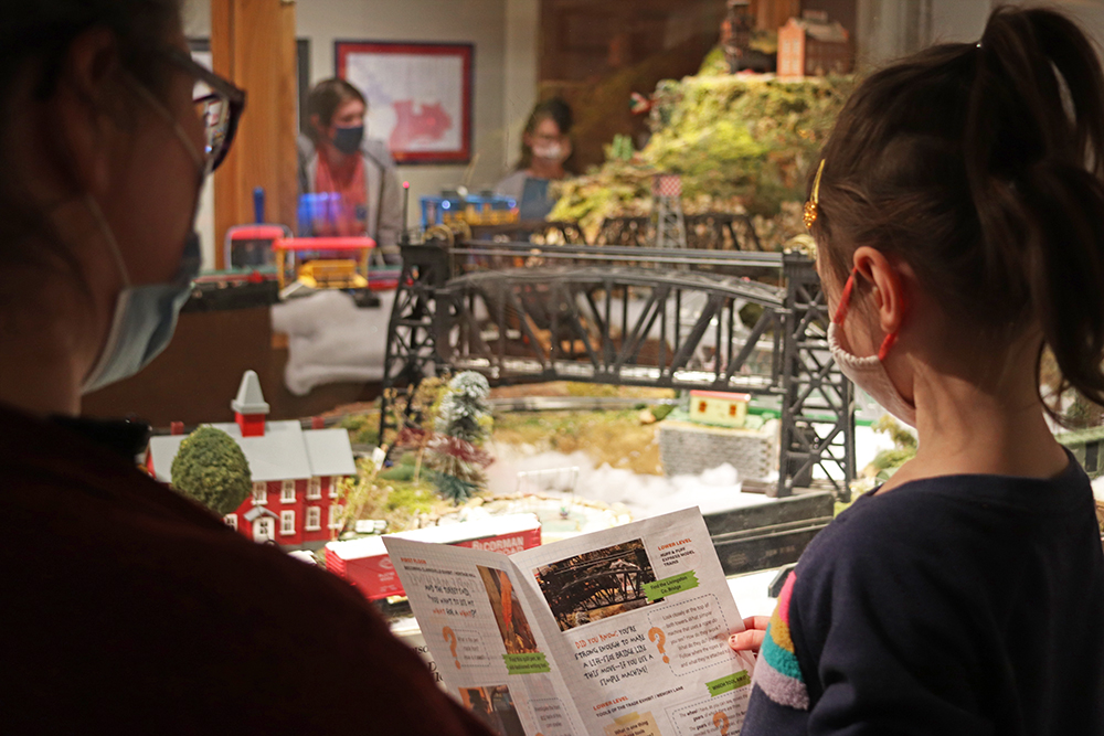 Mom and daughter view the Huff & Puff Express Model Trains. Daughter is holding a Museum Discovery Quest.