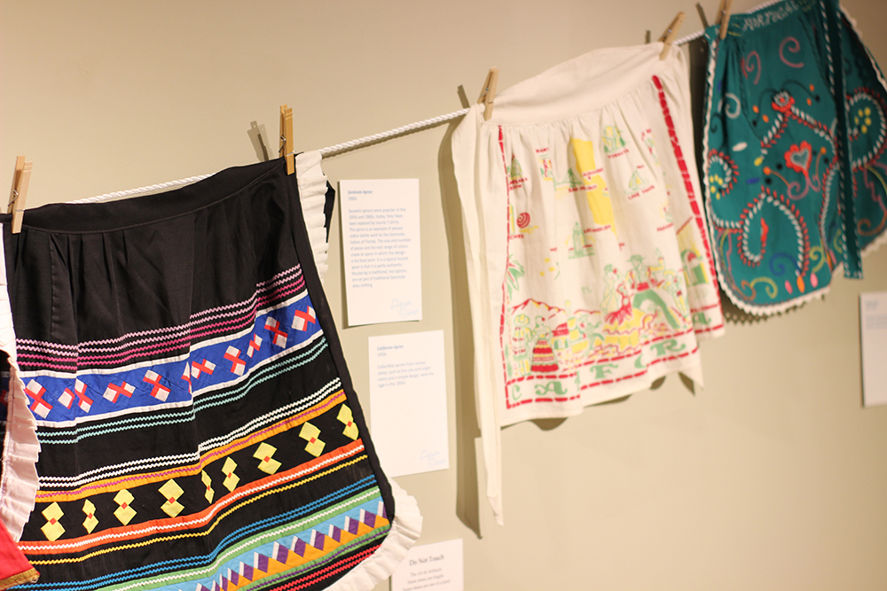Colorful aprons hanging on wall in gallery at the Customs House Museum.