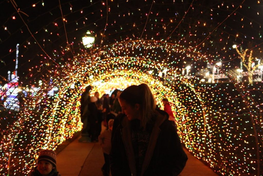 Nighttime scene of families under light arch at Christmas in Cumberland