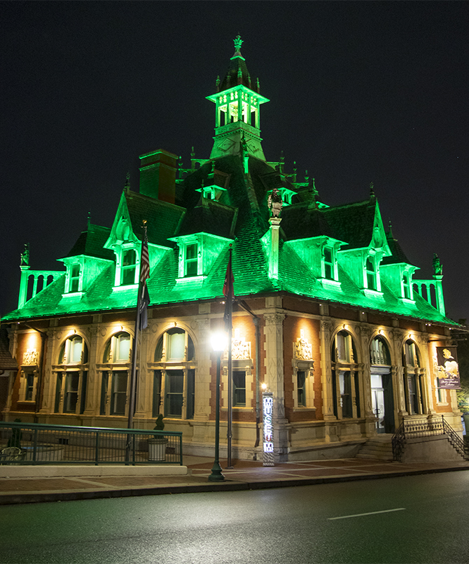 Nighttime scene of the Customs House Museum with an illuminated roofline of emerald green.