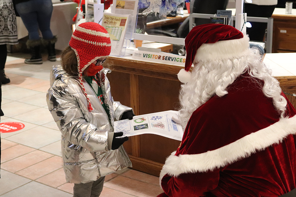 Santa hands a little girl an activity packet at Noel Night at the Museum.