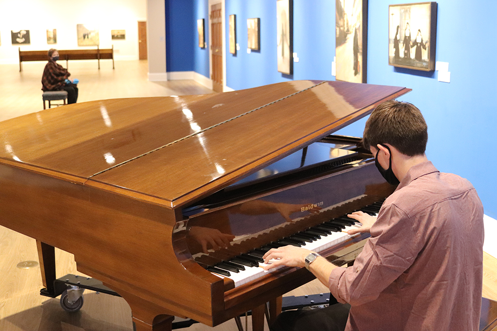 Pianist adds ambient music in the Orgain Gallery as Museum guests filter through from Noel Night.