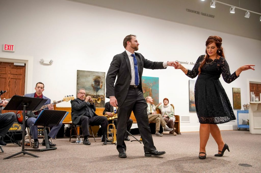 Museum guests dance in front of a live band in the Crouch Gallery during Champagne & Chocolate.