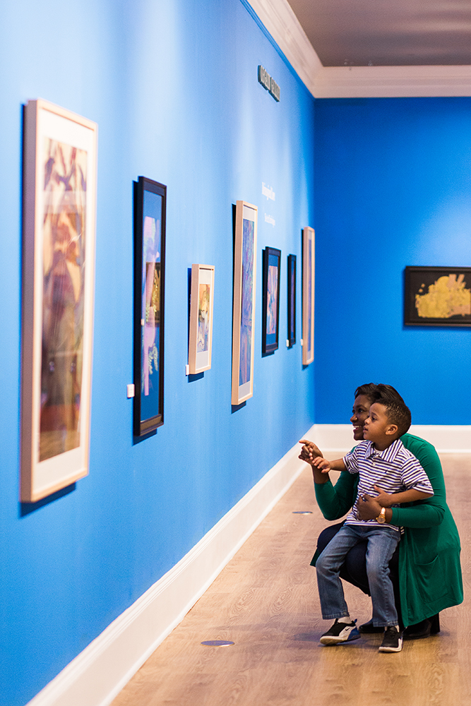 Mother and son stand in Orgain Gallery viewing an exhibit. Mother is pointing to a drawing on the wall.