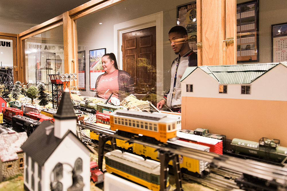 Two Museum guests watch the model trains glide by in the Huff & Puff Express Model Trains exhibit.