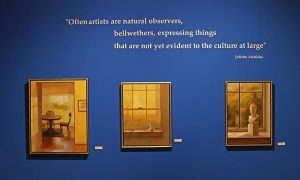 "Aristides' still life oil paintings hanging in the Orgain Gallery at the Customs House Museum & Cultural Center. Added to the wall is a quote from Juliette, ""often artists are natural observers, bellwethers, expressing things that are not yet evident to the culture at large."""