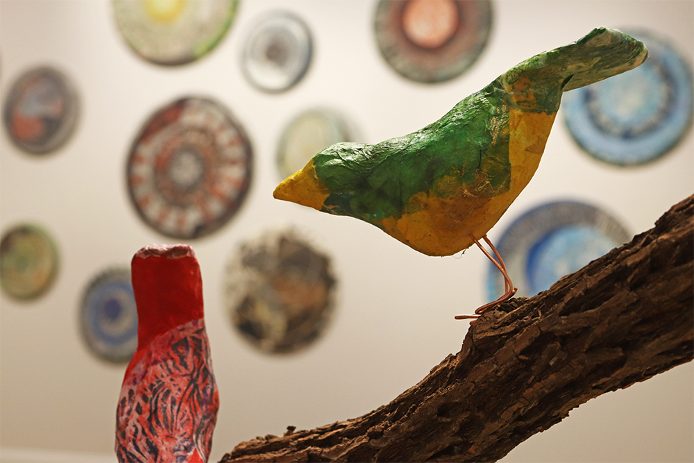 Papier-mâché birds sitting on a branch. Large decorative circular pieces are hanging on the wall in the background.