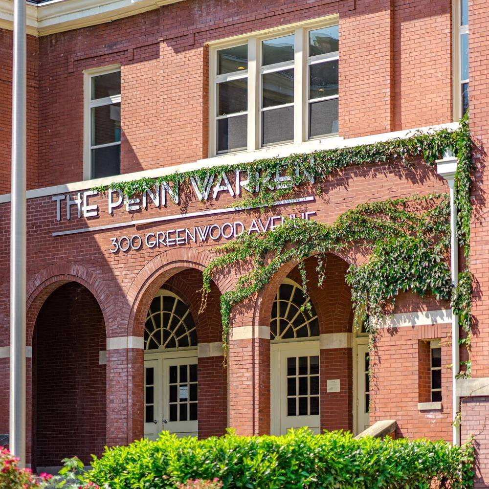 Entry way to the Penn Warren apartments. Brick building with greenery.