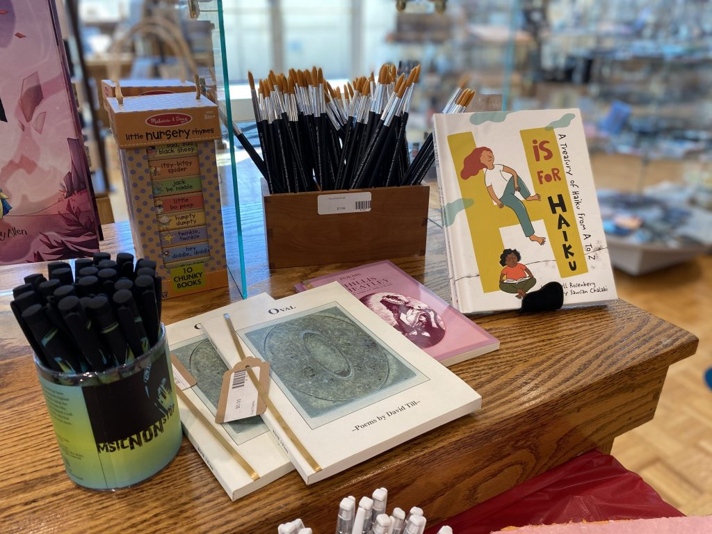 Gift shop display of pens, notebooks and books.