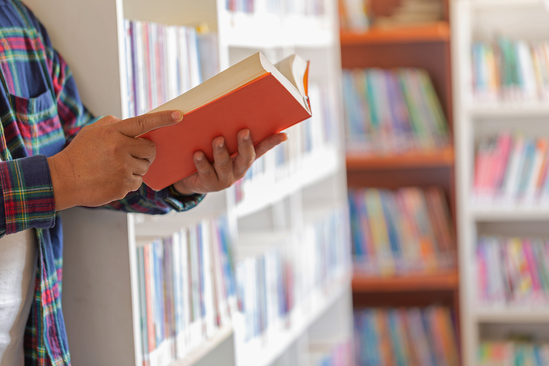 Image close-up of a person holding a book while standing around many bookshelves.