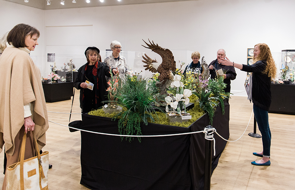 A group of older visitors peer at a Boehm porcelain display while a young tour guide motions towards the porcelain pieces.